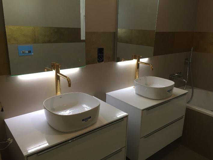 Lavabo y espejo de un baño moderno Descripción generada automáticamente