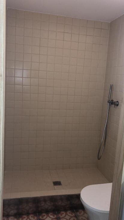 Una ducha con paredes de cristal  Descripción generada automáticamente con confianza media