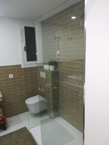 Una ducha con puertas de cristal  Descripción generada automáticamente con confianza media