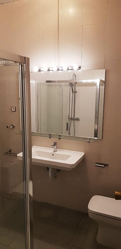 Una ducha con puertas de cristal  Descripción generada automáticamente