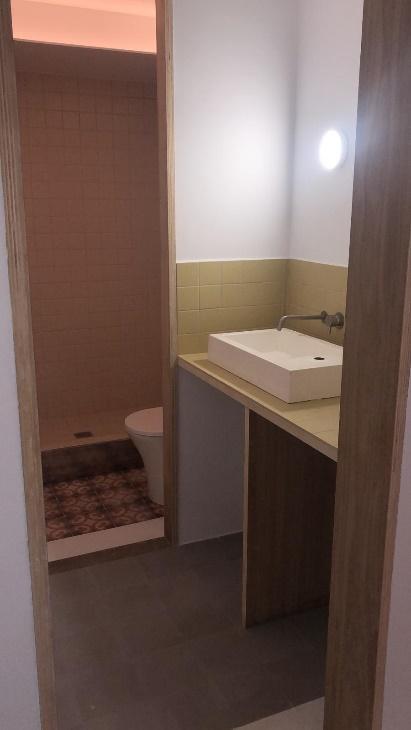 Una ducha con puertas de madera  Descripción generada automáticamente con confianza media