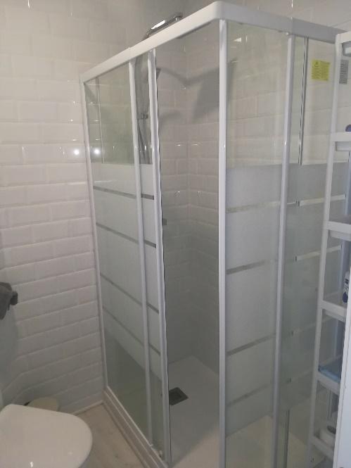 Una ducha con puertas de vidrio  Descripción generada automáticamente con confianza media