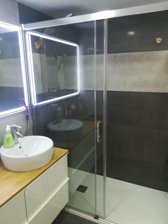 Una ducha con puertas de vidrio  Descripción generada automáticamente