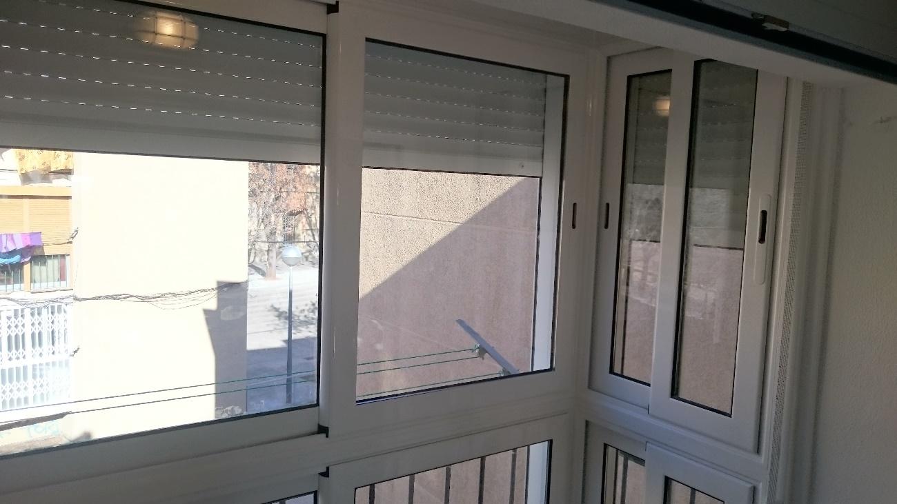 Una ventana con persianas blancas  Descripción generada automáticamente con confianza media