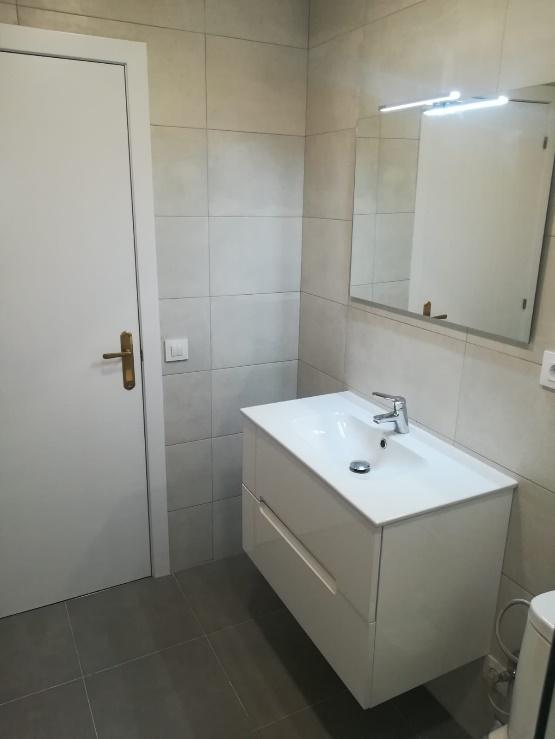 Un bano con un inodoro y un lavamanos  Descripción generada automáticamente con confianza media