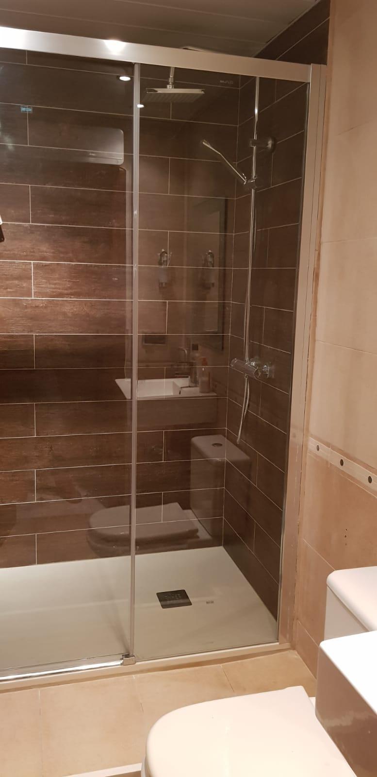 Una ducha con puertas de cristal  Descripción generada automáticamente con confianza baja